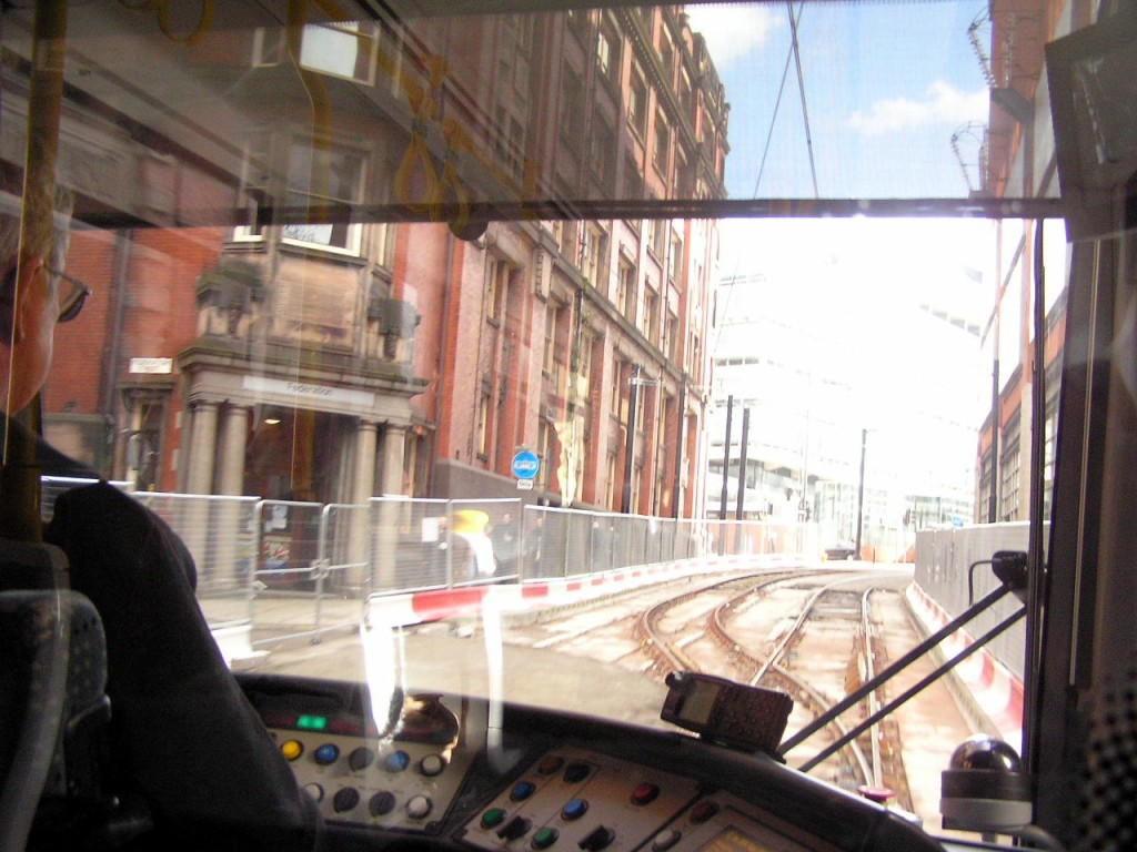 Looking through the driver's cab as the vehicle gets back off the single line.