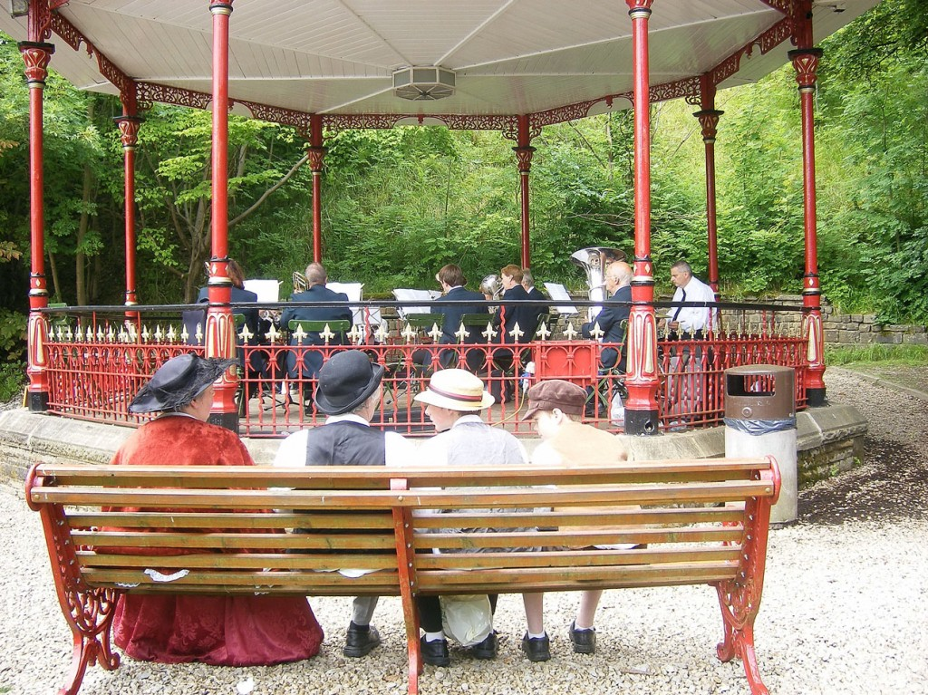 The bandstand being used for the purpose for which it is intended as people in Edwardian clothing look on.