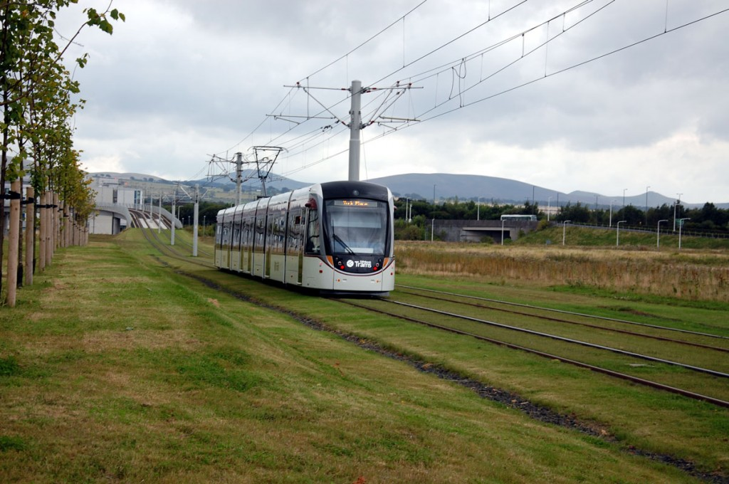 An unidentified tram on the grass covered tracks heading towards the city and the viaduct at Edinburgh Park station. The Pentland Hills are just visible on the skyline.