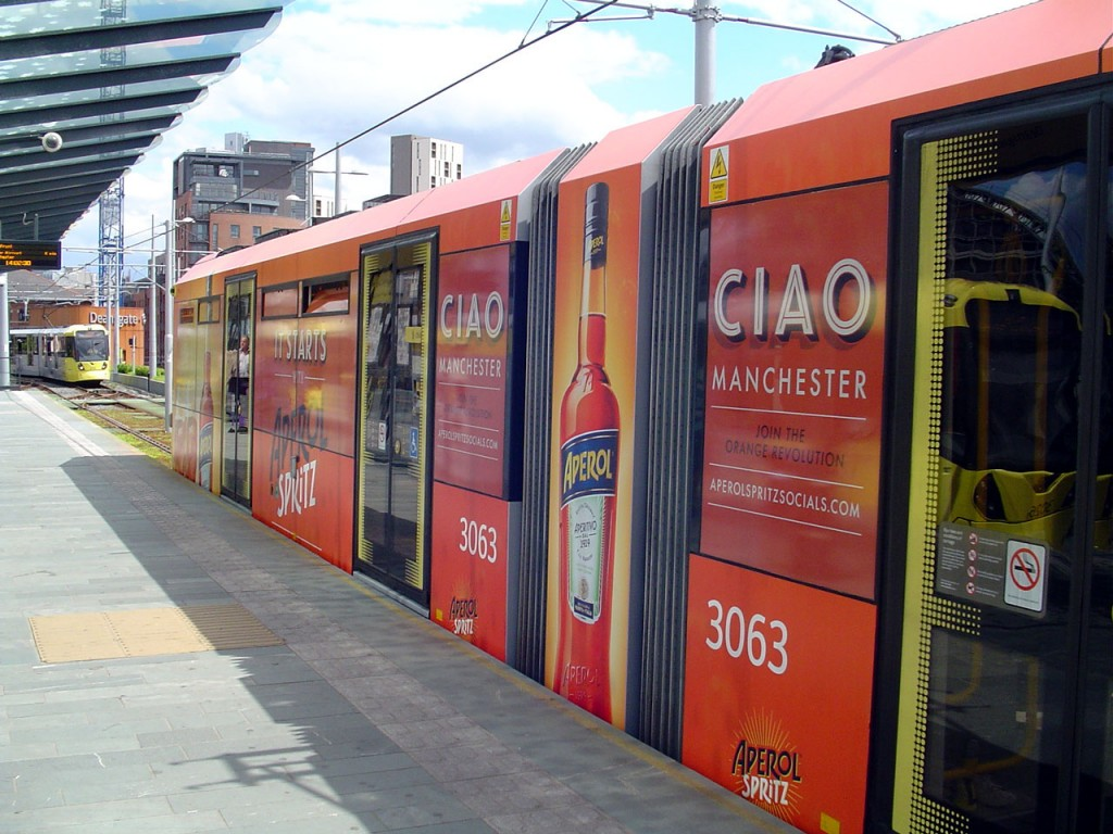 A close-up of the advertising vinyls on 3063 with two other trams also visible in the shot. (Both Photographs by Dave Elison)