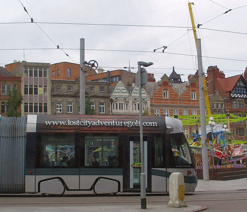 A side view of 203 as it passes a funfair in Old Market Square.