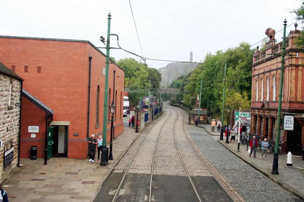 A view from the top deck of a tram as it starts off on its journey north. The Red Lion pub is on the right with the Workshop on the left. You can also see a couple of trams in the depot yard.