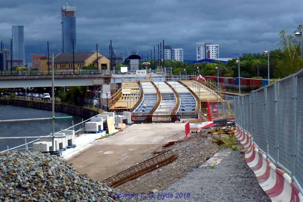This shot taken from the top of Pomona Strand is looking towards Pomona stop where a tram is waiting to depart towards MediaCityUK. We can see progress with the deck of the new bridge sections.