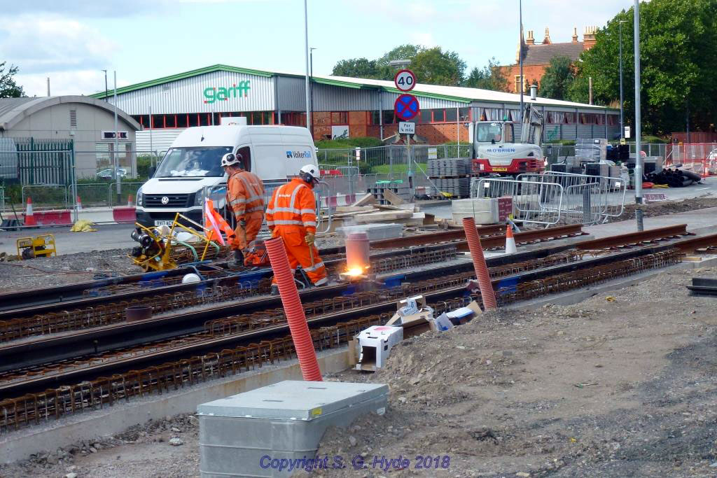 This photograph was taken at Village Circle near to Village stop where thermit welding of rail joints was in progress, rails are now installed on both lines through the Village Circle roundabout and right through Village stop except for a short gap approaching the stop.