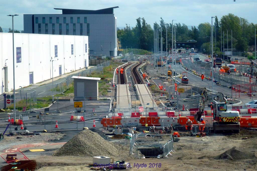 We are now at the Trafford centre on the footbridge linking Barton Square to the main shopping centre. This view looks east along Barton Dock Road and Event City is to the left. Track is in place for a considerable distance, in the background behind the grassed hump the alignment curves to the left to climb up to the new canal bridge.