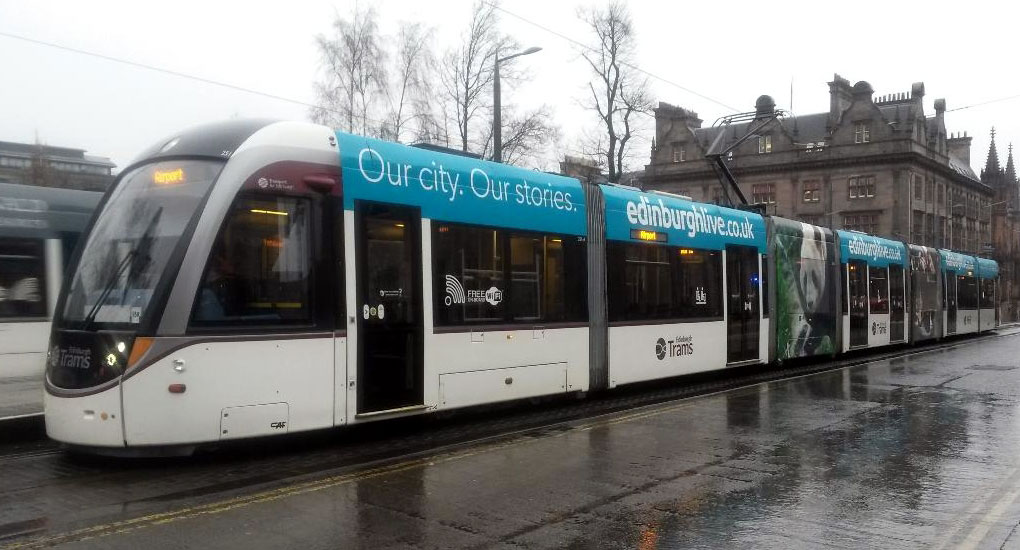 251 is captured in heavy rain at St Andrew Square on 5th February showing off its new advert for Edinburgh Live. This tram had been running temporarily without an advert having lost its ad for C R Smith in late January. (Photograph by John Hampton)