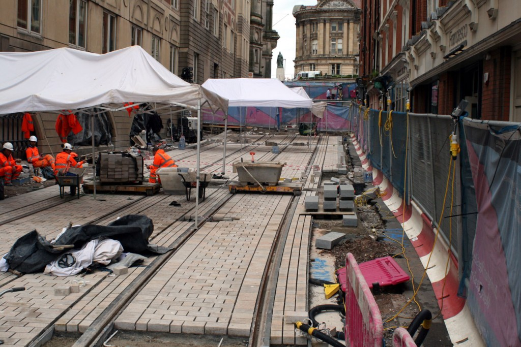 Pinfold Street with track in place and block paving being laid between the track.