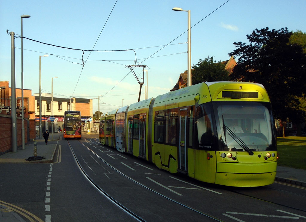 Having left Beeston Centre behind (the furniture on the platform can just be seen between the back of the bus and back of the tram Incentro 209 continues with its journey to Toton Lane. This tram carries a special livery promoting the tram as a good way to travel.