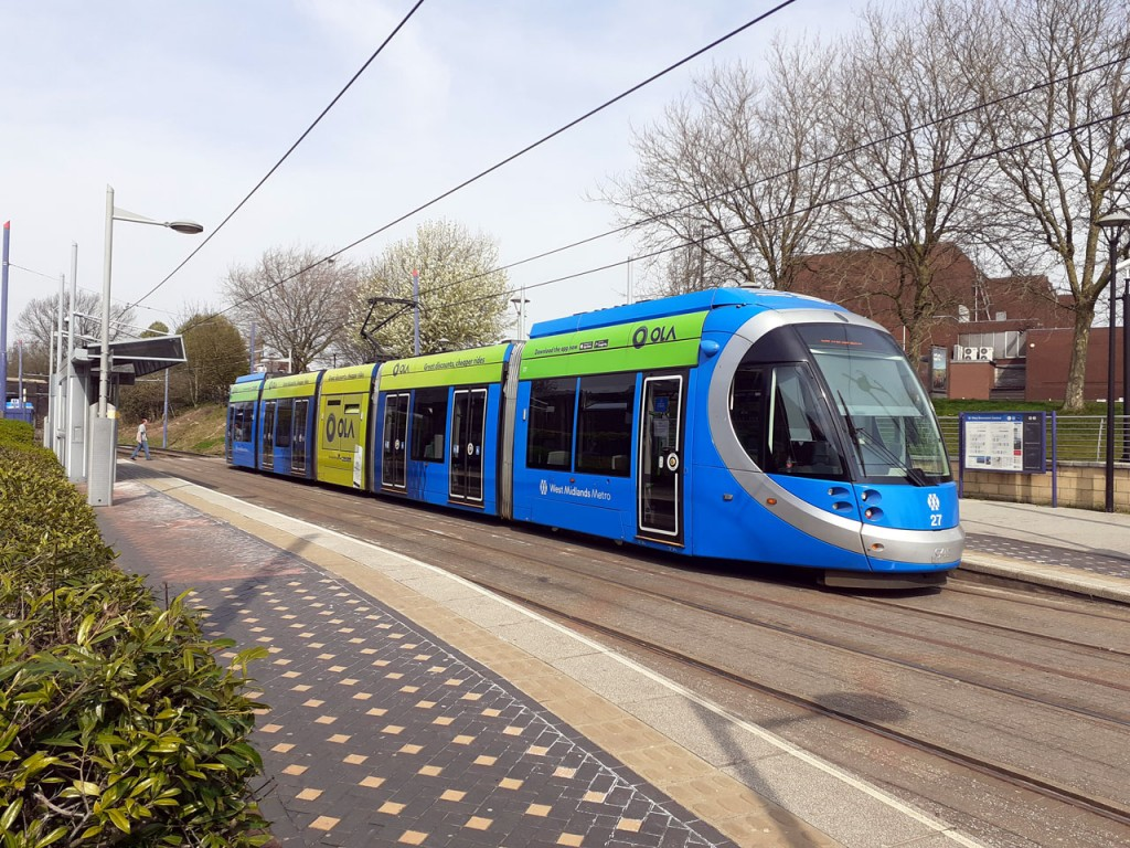 This photo we see 27 pausing at the stop on the way to Library in central Birmingham. This tram carried adverts for OLA, in the standard West Midlands Metro style featuring just a full height ad on the centre section. (Photograph by Andy Walters, 10th April 2020)