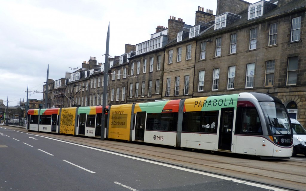 """In this view we see a Parabola adverted 274 just leaving York Place on 3rd April with a service which will run all the way through to Edinburgh Airport. The type of """"all over adverts"""" seen in Edinburgh can be clearly seen in this photo with the entire length of the tram having adverts above the windows and then the third and fifth sections full height adverts, for most this has included full coverage of the windows. (Photograph by Roy Calderwood, 3rd April 2020)"""